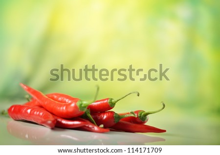 red hot chili pepper against green background - stock photo