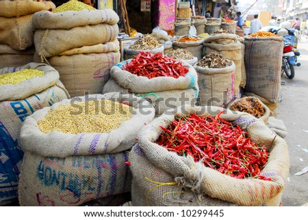 red hot chili pepper and other spices in jute gunny-bags on indian market - stock photo