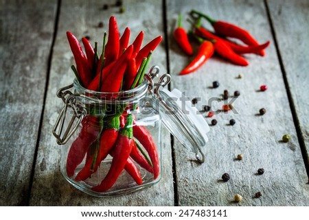 red hot chili pepper in a glass jar on a wooden background - stock photo
