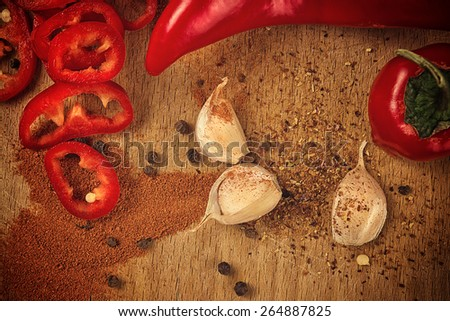 Red Hot Chili Pepper, Spice and Organic Garlic on Wooden Kitchen Plate as Hot Food Ingredients for Spicy Piquant Cuisine, top view - stock photo