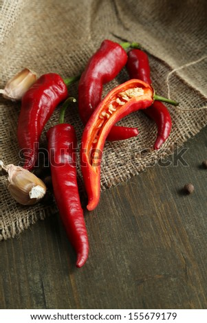 Red hot chili peppers  and garlic, on sackcloth,  on wooden background - stock photo