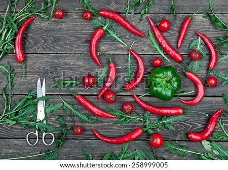 Red hot chili peppers and tomatoes on wooden background - stock photo