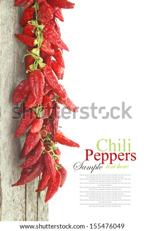 Red hot chili peppers hanging on wood, isolated on white - stock photo
