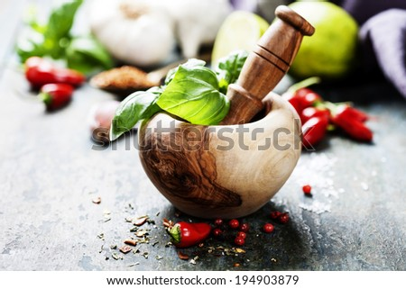 Red Hot Chili Peppers, herbs and spices with Mortar and Pestle over wooden background - stock photo