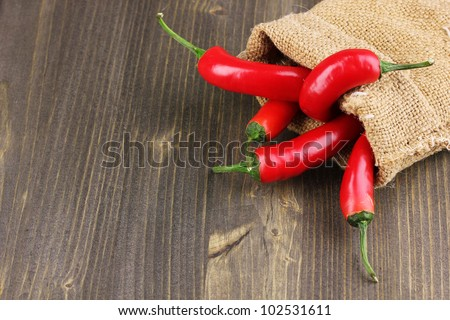 Red hot chili peppers in bag on wooden background