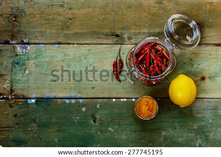 Red Hot Chili Peppers in glass jar over rustic wooden board - cooking or spicy food concept. Background with space for text. - stock photo