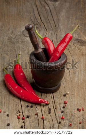 Red hot chili peppers in old wooden mortar and mix of dry pepper on old wooden table - stock photo