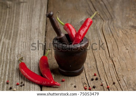 Red hot chili peppers in old wooden mortar on old wooden table
