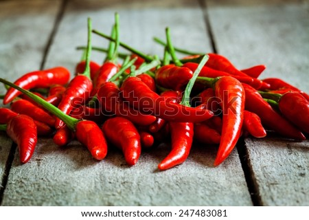 red hot chili peppers on a wooden rustic background - stock photo