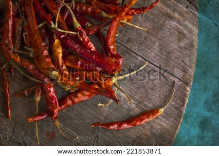 Red hot chili peppers on an old wooden table texture. Spicy pepper. Food photography with cope space. Shallow depth of field, selective focus