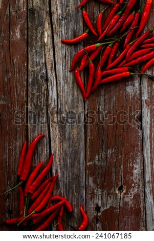 Red hot chili peppers on rustic wooden texture. Top view. - stock photo