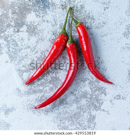 Red hot chili peppers over white textured background. With copy space. Top view. Square image - stock photo