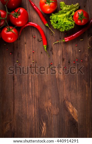 Red hot chilli peppers, tomatoes, lettuce, pepper seeds on old wooden table