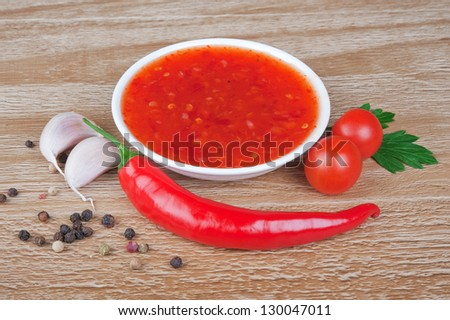 red hot chilli sauce over wooden background - stock photo