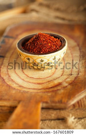red hot chillies pepper  flakes in bowl on wooden board  background, shallow dof - stock photo