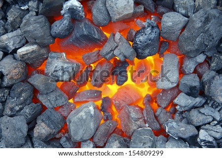 Red-hot coal smouldering in blacksmith furnace.  - stock photo