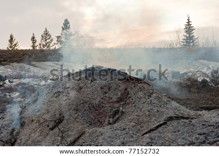 Red-hot coals still glowing and smoking under heap of ashes left from burning a pile of brush. - stock photo