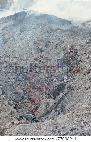 Red-hot coals still glowing and smoking under heap of ashes left from wood burning bonfire. - stock photo