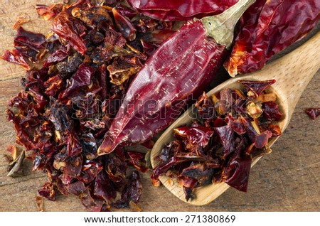 red hot dry chili pepper and crushed paprika on wood background - stock photo