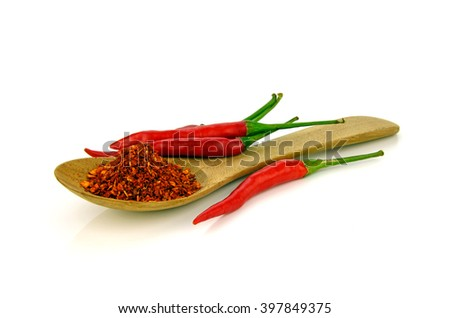 Red hot pepper chilli (Capsicum frutescens L.) with a spoon of cayenne pepper on white background. - stock photo