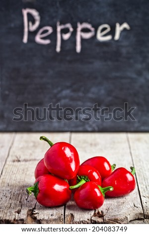 red hot peppers and blackboard on rustic wooden table - stock photo