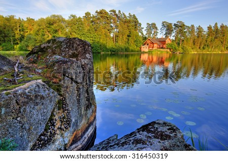 Red house and the lake rock - stock photo
