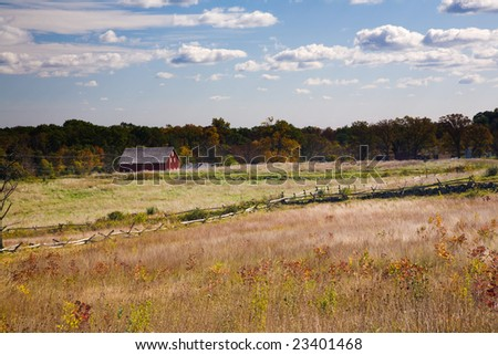 Red house in autumn field, forest in the background - stock photo