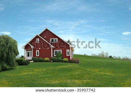 Red house in countryside with grass in foreground