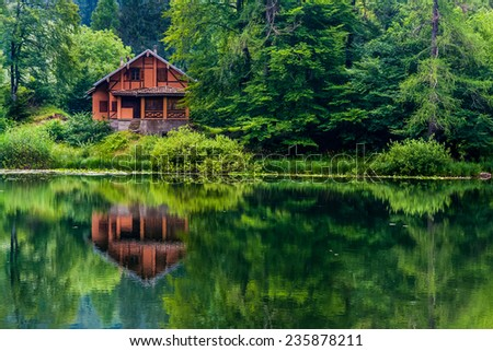 Red house in the middle of the nature with view of the lake - stock photo