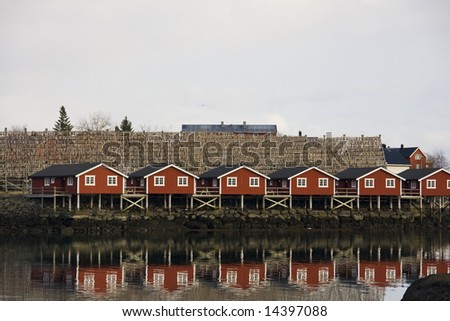Red houses on stilts at the sea, with stick fish - stock photo