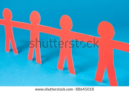 red human figures in a row on blue background. shallow DOF. - stock photo