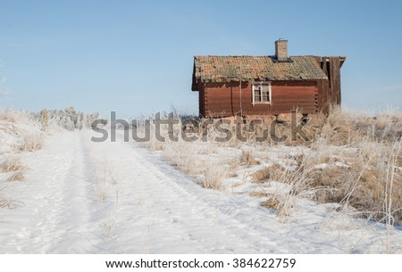 Red hut in winter in a frosty morning - stock photo