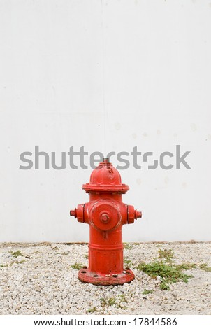 red hydrant in front of plain white fence - stock photo
