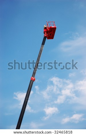 Red hydraulic cherry picker over blue sky - stock photo