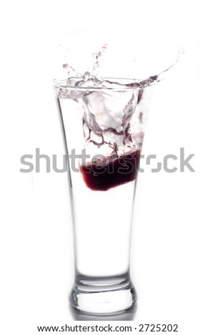 Red ice splashing into a water glass - stock photo