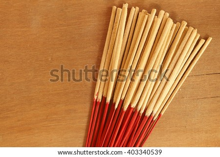 red incense sticks placed on a wooden floor. Used in religious rituals, prayers, worshiping various gods. - stock photo