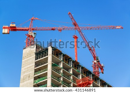 Red industrial construction crane against blue sky - stock photo