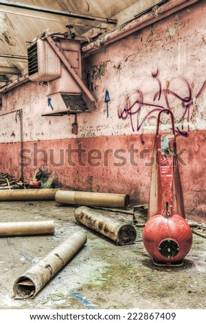 Red industrial fire extinguisher in an abandoned factory, HDR - stock photo