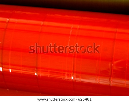 Red ink roller on printing machine for offset printing in the graphic industry - stock photo