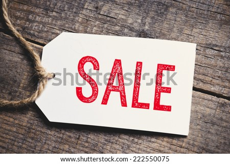 Red inscription Sale on blank tags on wooden table - stock photo