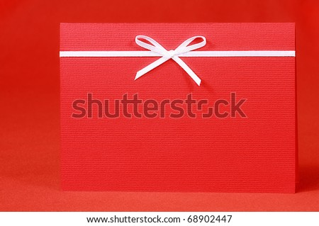 Red invitation card with bow on red silk satin background