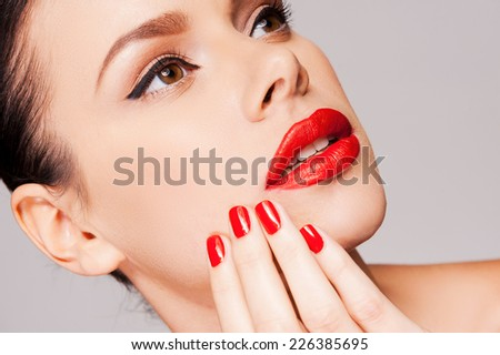 Red is a trend! Close-up of a beautiful woman holding fingers on face while standing against grey background