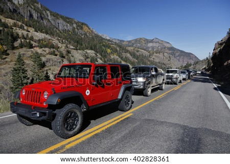 Red jeep and cars are delayed on Million Dollar Highway Route 550 out of Ouray Colorado during road repairs - stock photo
