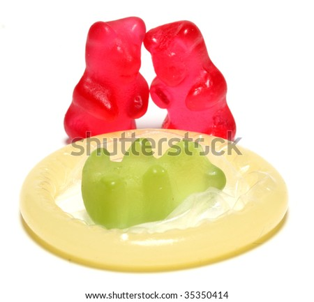 Red jelly bears parent and green jelly bear baby on a condom - conceptual image - on white background - stock photo
