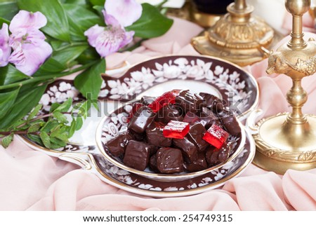 red jelly in chocolate on a plate in a luxury still life - stock photo