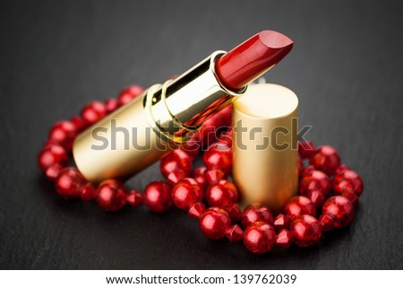 red  jewelry lipstick on black - stock photo
