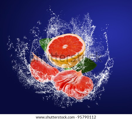 Red juicy segments of grapefruits with leaves in water splashes on the dark blue background - stock photo