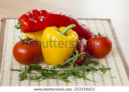 Red juicy tomatoes, leaves of arugula and sweet pepper - stock photo