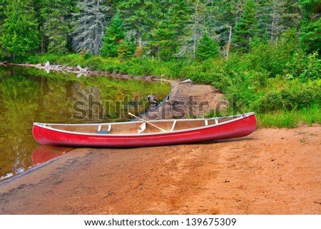 red kayak on the edge of a lake in Ontario Canada with two Canada geese in the background - stock photo