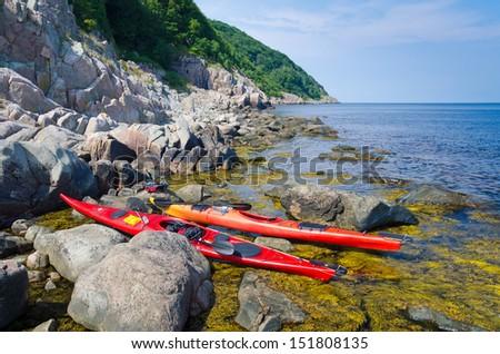 Red kayaks on rocky Swedish coast - stock photo